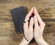Mãos que guardam a Bíblia e que rezam com um rosário Fotos de Stock