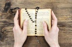 Mãos que guardam a Bíblia e que rezam com um rosário Imagem de Stock