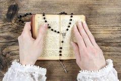 Mãos que guardam a Bíblia e que rezam com um rosário Imagem de Stock Royalty Free