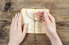 Mãos que guardam a Bíblia e que rezam com um rosário Foto de Stock