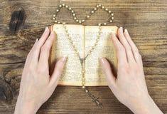Mãos que guardam a Bíblia e que rezam com um rosário Fotos de Stock Royalty Free