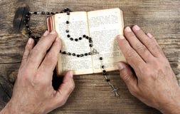 Mãos que guardam a Bíblia e que rezam com um rosário Fotografia de Stock