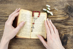 Mãos que guardam a Bíblia e que rezam com um rosário Imagens de Stock