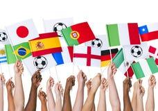 Mãos que guardam a bandeira para o apoio do futebol fotos de stock royalty free