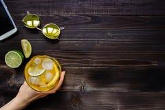 Mãos que guardam a bebida do gelo Chá de gelo, óculos de sol e smartphone na tabela de madeira, vista superior Com espaço da cópi Fotografia de Stock Royalty Free