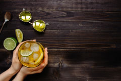 Mãos que guardam a bebida do gelo Chá de gelo, limão, cal e óculos de sol na tabela de madeira, vista superior Com espaço da cópi Imagem de Stock Royalty Free