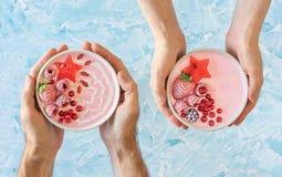 Mãos que guardam Berry Yogurt Smoothie Bowls cor-de-rosa fotografia de stock