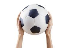 Mãos que guardam a bola de futebol foto de stock