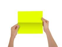 Mãos que guardam a brochura amarela vazia do folheto na mão leaflet fotos de stock