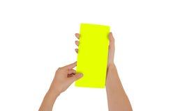 Mãos que guardam a brochura amarela vazia do folheto na mão leaflet imagem de stock royalty free