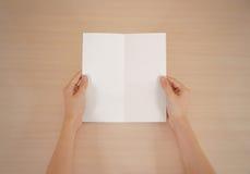 Mãos que guardam a brochura branca vazia do folheto na mão leaflet foto de stock royalty free