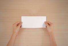 Mãos que guardam a brochura branca vazia do folheto na mão leaflet imagem de stock