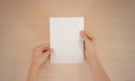 Mãos que guardam a brochura branca vazia do folheto na mão leaflet fotos de stock royalty free