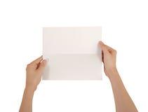 Mãos que guardam a brochura branca vazia do folheto na mão leaflet foto de stock