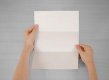 Mãos que guardam a brochura branca vazia do folheto na mão leaflet fotografia de stock royalty free