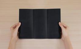 Mãos que guardam a brochura preta vazia do folheto na mão leaflet fotografia de stock