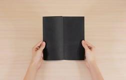 Mãos que guardam a brochura preta vazia do folheto na mão leaflet imagem de stock