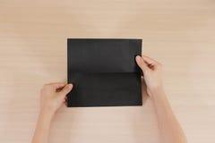 Mãos que guardam a brochura preta vazia do folheto na mão leaflet foto de stock