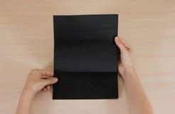 Mãos que guardam a brochura preta vazia do folheto na mão leaflet imagens de stock