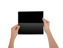 Mãos que guardam a brochura preta vazia do folheto na mão leaflet foto de stock royalty free