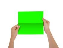 Mãos que guardam a brochura verde vazia do folheto na mão leaflet fotos de stock royalty free