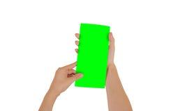 Mãos que guardam a brochura verde vazia do folheto na mão leaflet fotografia de stock royalty free