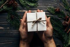 Mãos que guardam a caixa atual simples do Natal e que dão em à moda imagens de stock