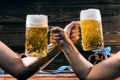 Mãos que guardam canecas de cerveja bávara Oktoberfest imagens de stock