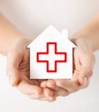 Mãos que guardam a casa de papel com cruz vermelha Fotografia de Stock Royalty Free