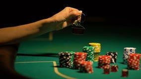 Mãos que guardam chaves à casa, microplaquetas de jogo ao redor, aposta tudo para bater o jackpot filme