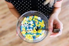 Mãos que guardam comprimidos farmacêuticos sortidos e cápsulas de uma medicina em uma bacia Imagens de Stock