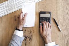 Mãos que guardam contas e contas pagando na tabela Foto de Stock