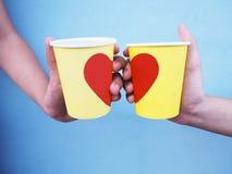 Mãos que guardam copos amarelos com forma vermelha do coração sobre a parede azul Fotos de Stock Royalty Free