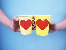 Mãos que guardam copos amarelos com forma vermelha do coração sobre a parede azul Fotografia de Stock