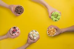 Mãos que guardam copos com gelado rolado diferente no fundo amarelo brilhante fotos de stock
