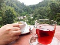 Mãos que guardam copos de café e que descansam em um vidro do chá no t Foto de Stock Royalty Free