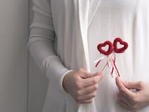 Mãos que guardam corações em varas fotos de stock