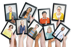 Mãos que guardam dispositivos de Digitas com caras do pessoa Imagens de Stock Royalty Free