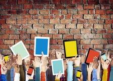 Mãos que guardam dispositivos de Digitas com telas coloridas Fotos de Stock
