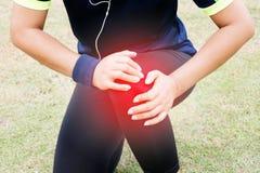 Mãos que guardam a dor do sentimento do joelho fotografia de stock royalty free