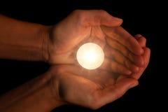 Mãos que guardam e que protegem a luz de vela iluminada ou de queimadura da vela na escuridão Imagem de Stock