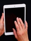 Mãos que guardam e que tocam em um PC da tabuleta Fotos de Stock