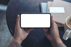 Mãos que guardam e que usam um telefone celular preto com tela vazia horizontalmente para olhar com copo e cadernos de café na ta fotografia de stock