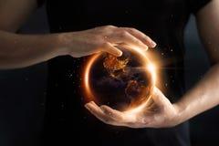 Mãos que guardam a exibição global o consumo de energia do ` s do mundo foto de stock royalty free