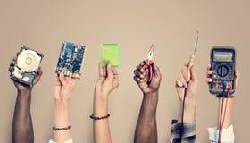 Mãos que guardam ferramentas da eletrônica no fundo marrom imagens de stock royalty free