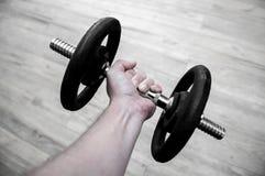 Mãos que guardam firmemente uma barra do gym com pesos do ferro imagem de stock
