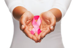 Mãos que guardam a fita cor-de-rosa da conscientização do câncer da mama Fotos de Stock Royalty Free