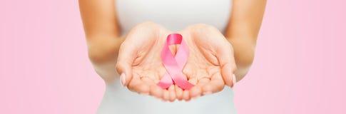 Mãos que guardam a fita cor-de-rosa da conscientização do câncer da mama Imagens de Stock Royalty Free