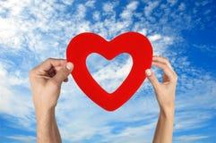 Mãos que guardam a forma do coração com céu azul Fotos de Stock Royalty Free