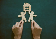 Mãos que guardam homens e a casa de madeira Imagens de Stock Royalty Free